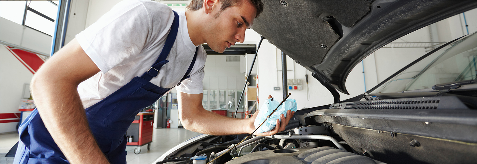 a repairman looks over the engine of a car in the shop