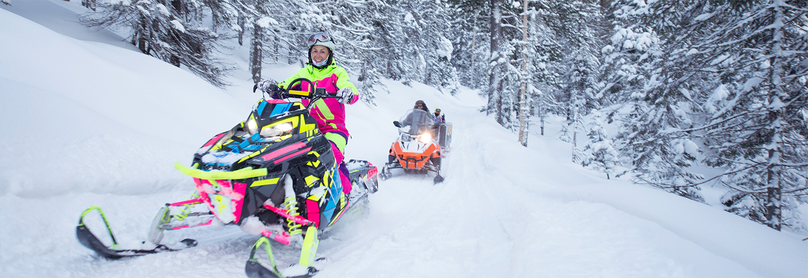 A photo of people on the trails in their snowmobiles, enjoying a beautiful winter day